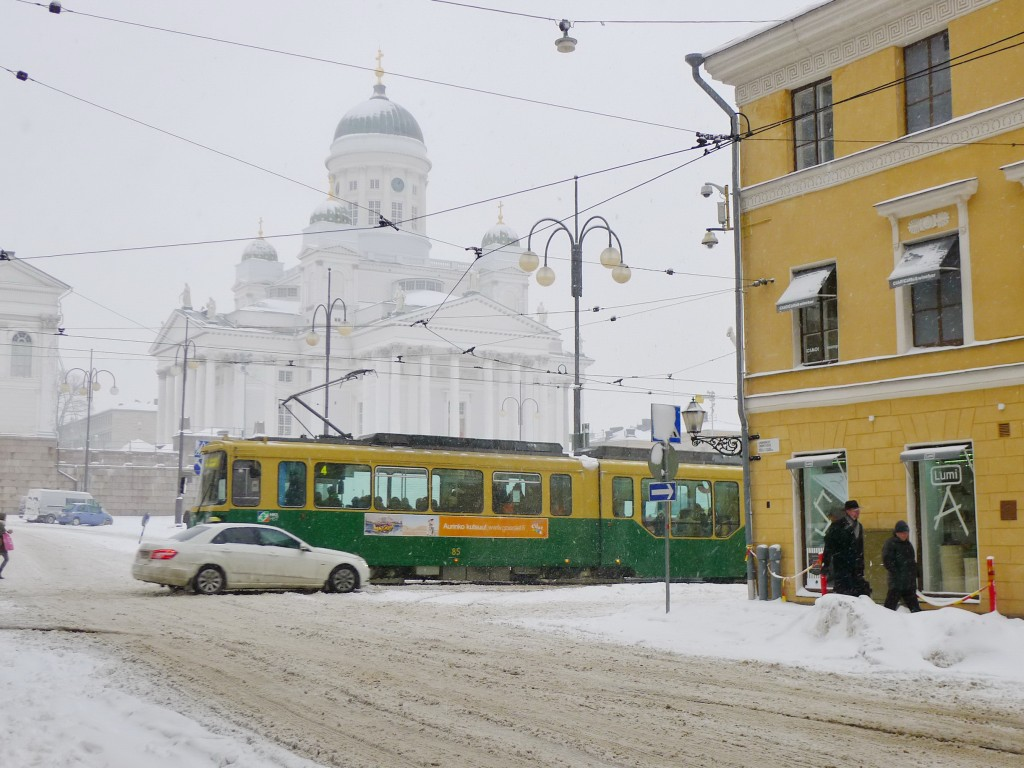 Ghostly image of Helsinki Cathedral in white behind a green tram and a yellow building