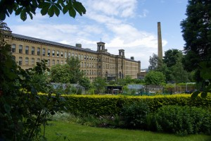 Massive buff-coloured factory with allotment gardens in front