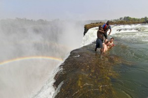 Visitors swim in Devil's Pool at Victoria Falls. It looks like they will be swept over the waterfall but a thick lip of rock keeps people safe. Photo by Yvette Cardozo