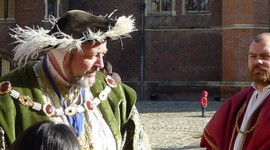 Large man in green velvet coat with gold chain around shoulders, black hat with white feathers trim, another man in red robe, no hat, in courtyard