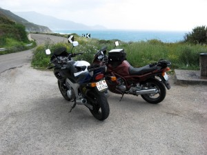 Two motorbikes parked by a road in Sardinia, Italy.