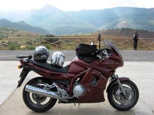 A motorbike parked next to a view of mountains, Sardinia, Italy.