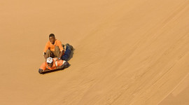 Two local boys sandboard down a dune near Swakopmund, a coastal city halfway up Namibia's Atlantic coast.