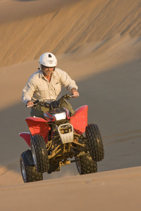 Swakopmund is Namibia's adventure capital with activities ranging from paragliding and sandboarding to riding camels and 'quad' bikes in the desert. Here, a man drives a quad bike (four wheel ATV) up the side of a sand dune.