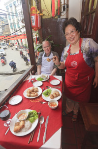 At a balcony table overlooking the historic Old Quarter of Hanoi,  celebrity chef Madam Pham Thi Tuet serves the finished spring rolls to the cooking student. Photo by Yvette Cardozo