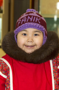 Little Inuit (Eskimo) girl in Churchill, Manitoba, Canada. Her hat says 'daughter' in Inuktitut, the Inuit language. Photo by Yvette Cardozo