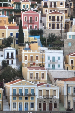 Steep hills surrounding Symi make homes look stacked.