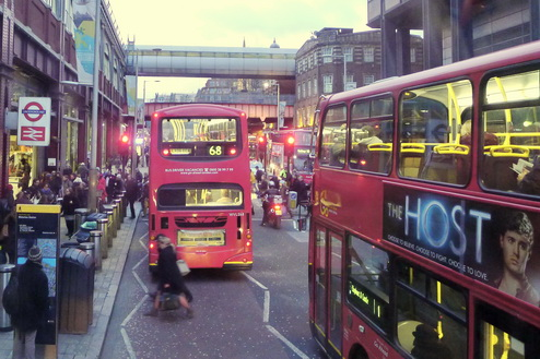 A woman darts in front of an oncoming red London bus on a street full of buses