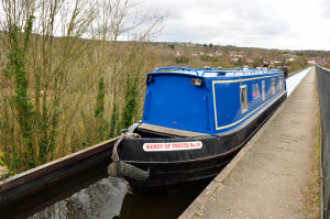A narrow boat barely fits into the trough of the aqueduct, which is completely open on one side. (photo credit: Katherine Rodeghier c 2013)