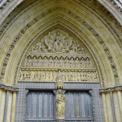 A dark double door set in the bottom half of a great Gothic arch of yellow-brown stone. The arch is filled with carvings of people.