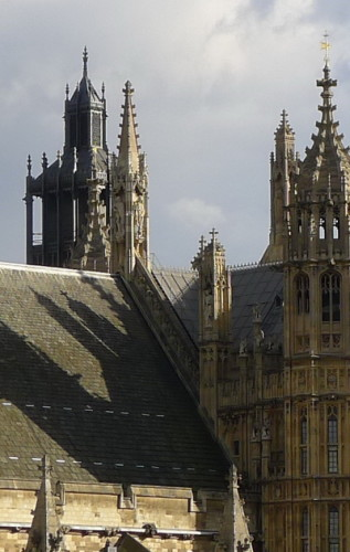 Detail of a roofline showing numerous Gothic points on a brown building, and their shadow on the the roof.