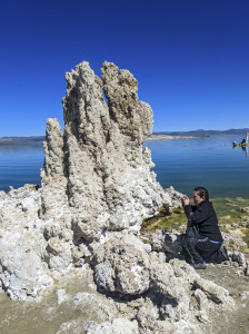 Woman photographs a tufa tower at the shoreline of Mono Lake