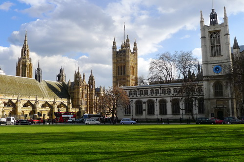 Green grass. To the left, brown Gothic Houses of Parliament. To the right, white church with square tower.