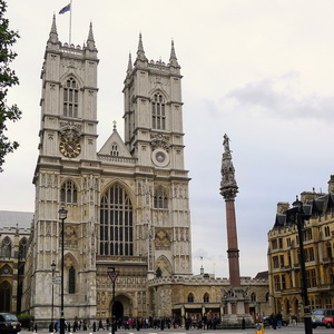A square, solid building with a massive Gothic pointed window, and two square towers on each side of the top. In front is a statue on a tall column.
