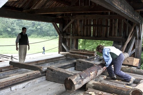 Preparing logs at the water-powered sawmill (Photo copyright Stillman Rogers)