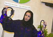 Young Arab woman in traditional Muslim hijab dress. Dubai, UAE. She is speaking to visitors at the Sheikh Mohammed Centre for Cultural Understanding where local people and visitors can meet to learn more about each other's culture.  Here she is showing various kinds of head gear worn by men. Photo by Yvette Cardozo