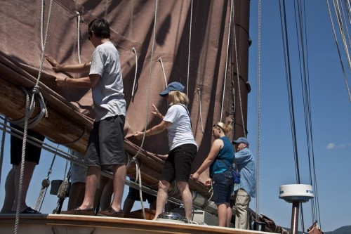 Mary and  other passengers helping furl Angelique sail (Photo by Stillman Rogers)